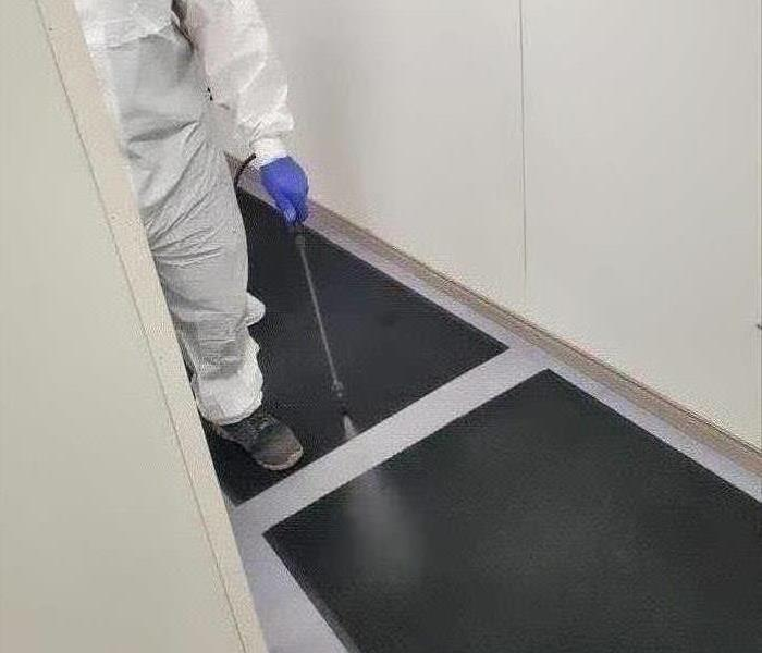 worker in white suit spraying black carpet